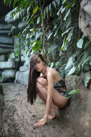 loose hair: Stylish girl with loose hair squats on the toes near the stone wall with green plants. She wears a colorful swimsuit with pictures. Her right hand is on the left knee, left hand is on the ground. Hairstyle hides her right eye. She looks into the camera wi