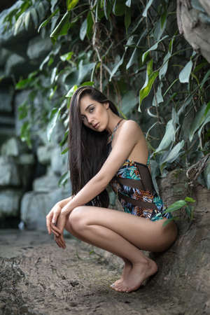 loose hair: Nice girl with loose hair squats on the toes near the stone wall with green plants. She wears a colorful swimsuit with pictures. Her crossed hands are on the knees. She looks into the camera with parted lips. Vertical.