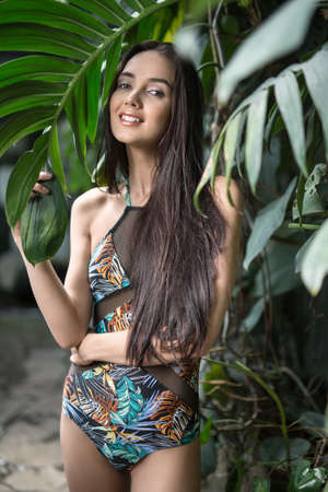 loose hair: Smiling girl with loose hair stands near the wall with big green plants. She wears a colorful swimsuit with pictures. She holds big leaf with the right hand, left hand is on the right hip. She looks into the camera. Vertical. Stock Photo