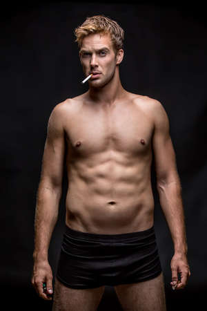Guy with muscular body in black underpants stands on the black background in the studio. He has a cigarette and a lighter in the hands and a cigarette in the mouth. Vertical low-key photo. Stock Photo
