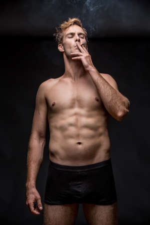 underpants: Young man with muscular body in black underpants stands on the black background in the studio. He smoke a cigarette and holds it with left hand. Vertical low-key photo. Stock Photo