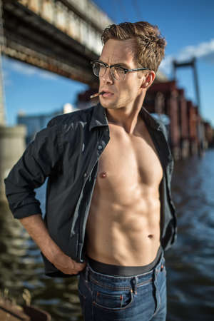 cute guy: Cute guy in glasses and in a dark unbuttoned shirt and blue jeans stands outdoors on the background of the bridge and the river. He smokes a cigarette. Guy looks to the right side. Vertical.
