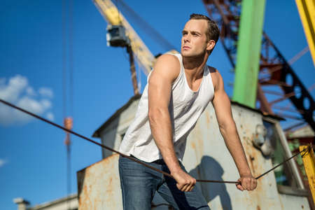 white singlet: Young man in a white singlet and blue jeans holds the steel rope on the background of industrial zone and blue sky. He looks to the right. Outdoors. Horizontal. Stock Photo