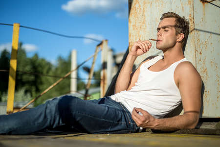 white singlet: Trendy guy in a white singlet and blue jeans lies with closed eyes on the industrial building on the background of the blue sky. He smokes a cigarette. Outdoors. Horizontal.