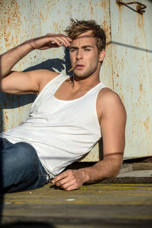 white singlet: Cute guy in a white singlet and blue jeans lies on the industrial building. He smokes a cigarette. Man looks in front of himself and holds the right hand near his face. Outdoors. Vertical.