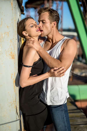 white singlet: Attractive couple with closed eyes shows their passion in the industrial zone. Guy wears a white singlet and blue jeans, girl wears a black dress. Outdoors. Vertical.