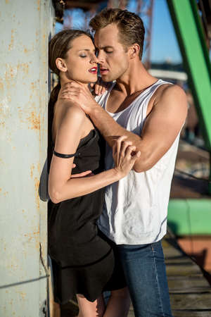 white singlet: Beautiful couple shows their passion in the industrial zone. Guy wears a white singlet and blue jeans, girl wears a black dress. Outdoors. Vertical. Stock Photo