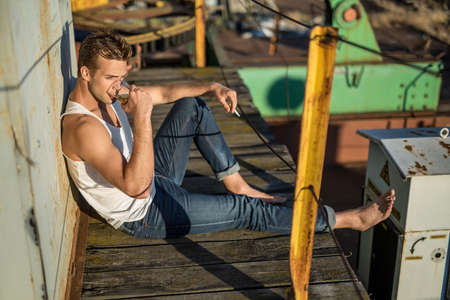 white singlet: Trendy barefoot guy in a white singlet and blue jeans lies on the wooden surface in the industrial zone. He drinks from the glass in the right hand, left hand holds a cigarette. Outdoors. Horizontal.
