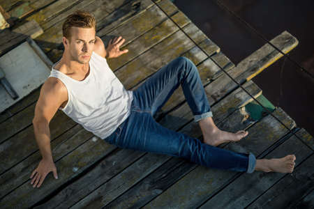 white singlet: Cute barefoot guy lies on the wooden surface outdoors. He wears a white singlet and blue jeans and looks into the camera while leans on his hands. Photographed from the upper point. Horizontal. Stock Photo
