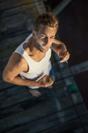 casual men: Cool barefoot smoker in a white singlet and blue jeans stands on the wooden surface outdoors. Guy exhales the smoke. He holds a glass in the right hand and a cigarette in the left. Vertical.