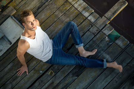 white singlet: Brutal barefoot guy lies on the wooden surface outdoors. He wears a white singlet and blue jeans and looks into the camera while smokes a cigarette. Photographed from the upper point. Horizontal.