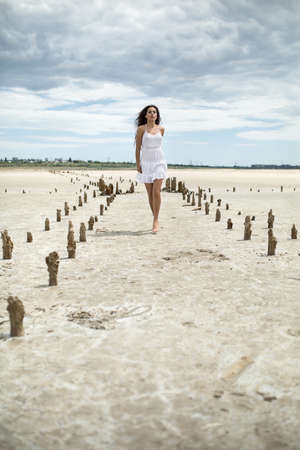 sides: Cute barefoot girl walks on the sand on the cloudy sky background. She wears white dress. She looks in front of herself. There are wooden pillars on the sand on the sides of the girl. Outdoors. Vertical. Stock Photo