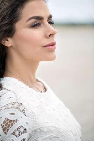 lace like: Portrait of a beautiful brunette in a white lace dress. Girl walking on sandy estuary looked like a desert.