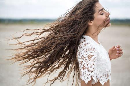 Portret van een mooie brunette in een witte kant jurk. Meisje dat op een zandmonding loopt, lijkt op een woestijn. Stockfoto