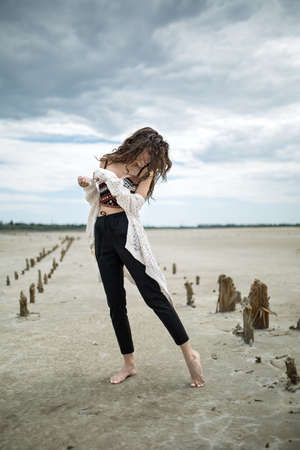 black toes: Attractive barefoot girl stands on the sand on the cloudy sky background. She wears black pants, multi-colored top with patterns and a white cardigan. Her arms bended in elbows are in front of her torso. Her left leg is on the toes and she looks on it. Th Stock Photo
