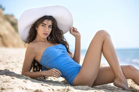 leans on hand: Stylish model in the blue swimsuit and the white hat lies on the sand on the background of the rocks, the sea and the sky. She holds the hat with the right hand. She leans on the right elbow, right leg is bended in the knee. She looks to the side with par Stock Photo