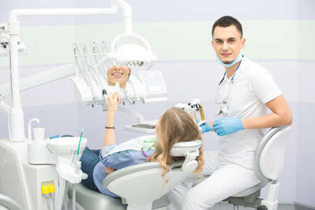 articulator: Smiling dentist in the dental cabinet. He is in the white uniform with blue latex gloves, blue mask, binocular loupes. He sits on the chair and holds an articulator with teeth mould. Next to him on the patient chair sits a girl in the blue shirt, jeans an Stock Photo