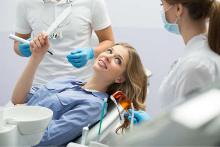 latex girl: Smiling girl in blue shirt with a mirror in the right hand on the patient chair in the dental cabinet. Next to her there is a dentist and a female assistant. They both wear white uniform with blue latex gloves and blue masks. Dentist also has binocular lo Stock Photo