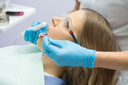 protective eyewear: Young girl with opened mouth in patient bib and protective eyewear. Next to her there is a dentist in a white uniform with blue latex gloves. He diagnoses her teeth with a LED intraoral camera and a stem mouth mirror. Horizontal. Stock Photo