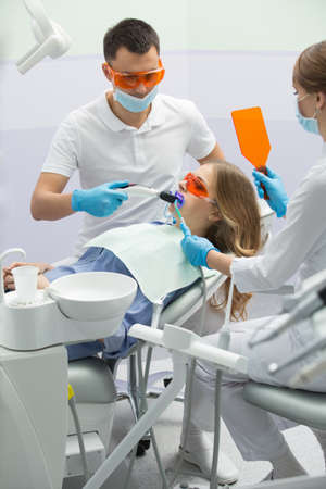 Cute girl in blue shirt and patient bib on the patient chair in the dental cabinet. Next to her there is a male dentist and a female assistant. They both wear white uniform with blue latex gloves and blue masks. Patient and dentist wear UV protective eyew