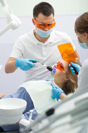 Brave girl in blue shirt and patient bib on the patient chair in the dental cabinet. Next to her there is a male dentist and a female assistant. They both wear white uniform with blue latex gloves and blue masks. Patient and dentist wear UV protective eye Stock Photo
