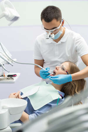 protective eyewear: Male dentist and a female patient. He is in the white uniform with blue latex gloves, blue mask, binocular loupes. She is in the blue shirt on the patient chair. She has a patient bib and a protective eyewear. Dentist treats her teeth with a LED handpiece