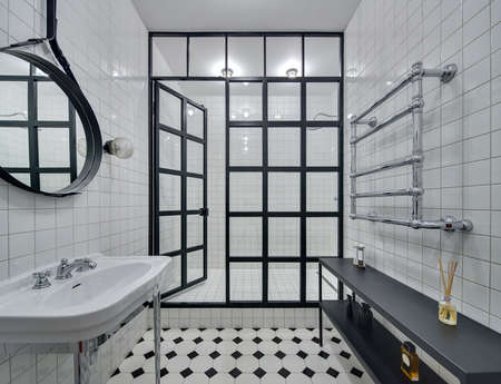 Bathroom with walls of white tiles. There is white washbasin, black mirror, shower with glass partition with open door and glowing lamps, black rack with accessories and chromed heated towel rail.