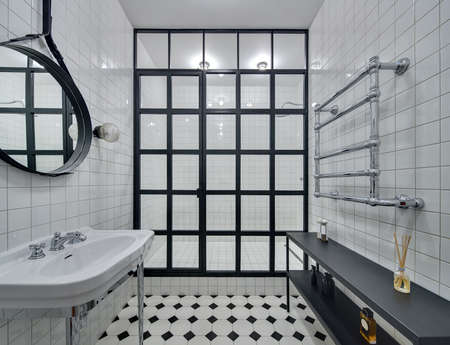 chromed: Bathroom with walls of white tiles. There is white washbasin, black mirror, shower with black partition of glass squares and glowing lamps, black rack with accessories and chromed heated towel rail. Stock Photo