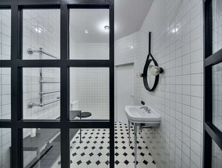 chromed: Modern bathroom with walls of white tiles. There is white washbasin, black mirror, lamps, glass partition, white-black toilet, black rack with accessories, chromed heated towel rail, white door. Stock Photo