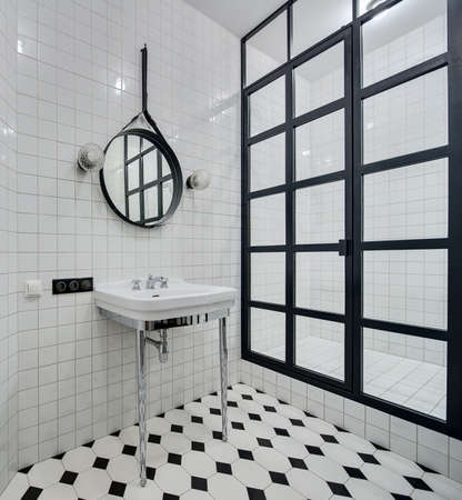 chromed: Design bathroom with walls of white tiles. There is white washbasin with chromed legs and faucet, black mirror with two lamps, shower with black partition of glass squares and glowing lamp.
