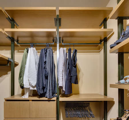 crossbars: Wardrobe with wooden shelves and drawers. On crossbars hang clothes and hangers, on shelves stand shoes.