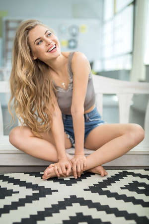 barefoot blonde: Blonde barefoot girl sits with crossed legs at home and looks to the left with a smile. She wears a singlet and denim shorts. Her hands are on the left leg. Indoors. Vertical. Stock Photo
