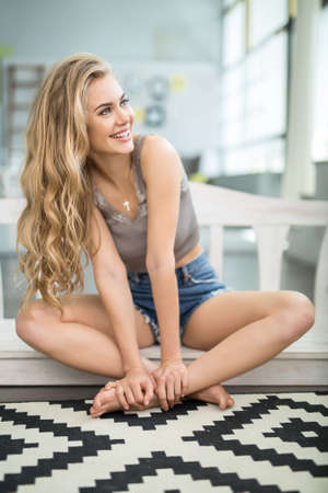 singlet: Beautiful barefoot girl sits with crossed legs at home and looks to the left with a smile. She wears a singlet and denim shorts. Her hands are on the left leg. Indoors. Vertical.