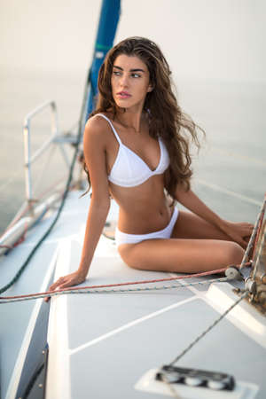 leans on hand: Model girl in a white swimsuit sits on the yacht and looks to the right with parted lips on the sea background. She leans on the right hand while left hand is on the left knee. Outdoors. Vertical.