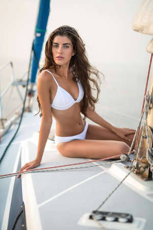 leans on hand: Sun-tanned girl in a white swimsuit sits on the yacht and looks into the camera with parted lips on the sea background. She leans on the right hand while left hand is on the left knee. Vertical.