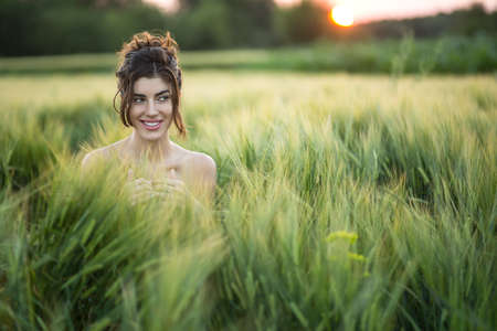 joyous: Joyous girl sits in the rye field and looks to the side with a smile on the sunset background. She holds her hands together.  Outdoors. Horizontal. Stock Photo