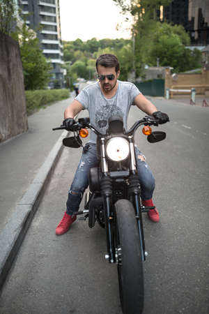 Young man on the black motorcycle on the urban background. He wears blue ripped jeans, a gray T-shirt with print, red sneakers, black moto gloves and sunglasses. He has a beard. He has a bracelet on the right hand and the watches on the left hand. Outdoor