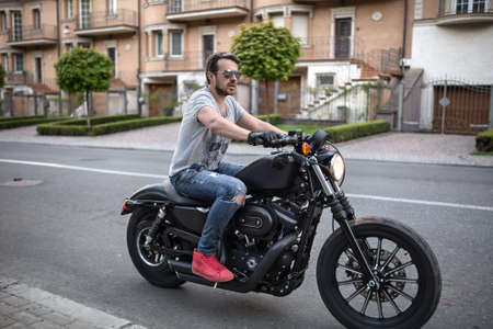 Handsome man on the black motorcycle on the urban background. He wears blue ripped jeans, a gray T-shirt with print, red sneakers, black moto gloves and sunglasses. He has a beard. He has a bracelet on the right hand. Photographed from the side. Outdoors.