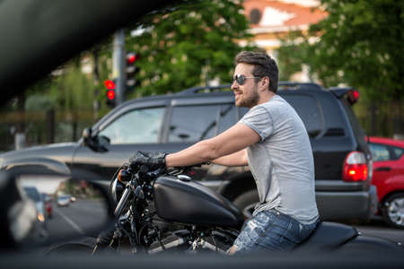 attractive charismatic: Smiling man on the black motorcycle stands in the traffic before the red traffic light. He wears blue ripped jeans, a gray T-shirt, black moto gloves and sunglasses. He has watches on the left hand. Photographed from the side. Outdoors. Horizontal.