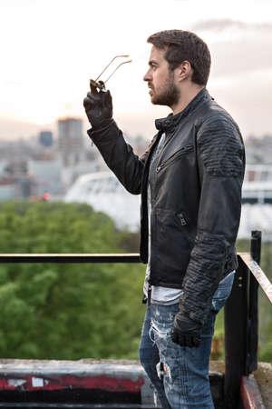Trendy man staat zijwaarts op de stedelijke achtergrond. Hij houdt zonnebril in de rechterhand. Hij draagt blauwe gescheurde spijkerbroek, een grijs T-shirt, zwarte moto handschoenen en zwarte leren jas. Hij kijkt voor zich. Buitenshuis. Verticaal. Stockfoto
