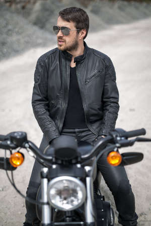 attractive charismatic: Attractive man with a beard on the black motorcycle on the blurry background outdoors. His hands lies on his legs. He looks to the left. He wears black jeans, a black T-shirt, black moto gloves, a black leather jacket and sunglasses. Vertical. Stock Photo