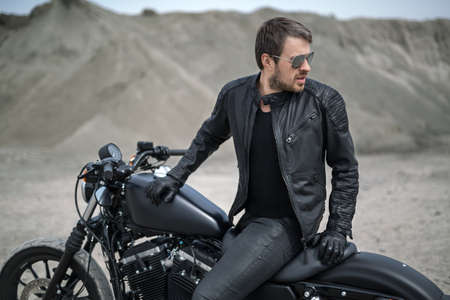 attractive charismatic: Trendy man sits on the black motorbike on the blurry background outdoors. His torso partially turned to the left, hands are on the motorbike. He looks to the left. He wears black jeans, a black T-shirt, black gloves, a black leather jacket and sunglasses.