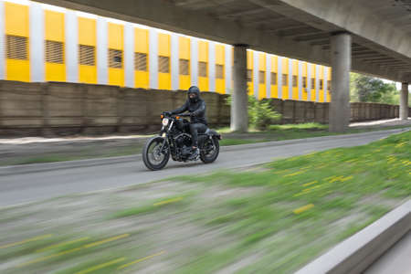 Guy in black helmet hurtling on the black motorbike on the road under the overpass. He wears a black leather jacket, black jeans, black shoes, black gloves and sunglasses. Outdoors. Horizontal. Stock Photo