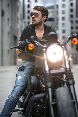 Bearded man sits on the black motorbike on the skyscraper background. Headlamp switched on. He wears a blue ripped jeans, a black T-shirt, black gloves and sunglasses. He looks to the right with parted lips. Black helmet lies on the motorbike in front of