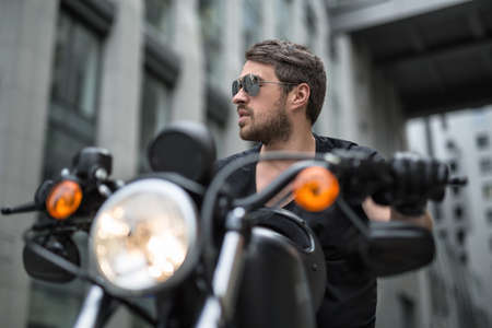 Charismatic man sits on the black motorbike on the skyscraper background. Headlamp switched on. He wears a black T-shirt, black gloves and sunglasses. He looks to the right with parted lips. He holds hands on the rudder. Black helmet lies on the motorbike Stock Photo