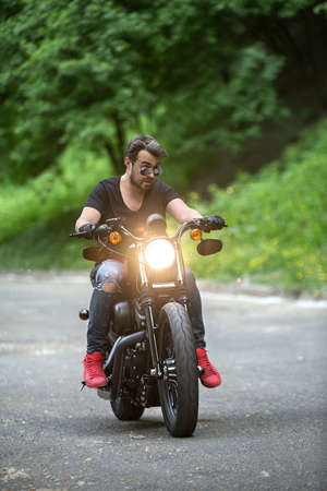 Stylish man with a beard rides on the black motorbike on the green tree background. Headlamp switched on. He looks frowningly to the left. He wears blue ripped jeans, a black T-shirt, black gloves, red sneakers and sunglasses. Outdoors. Vertical.