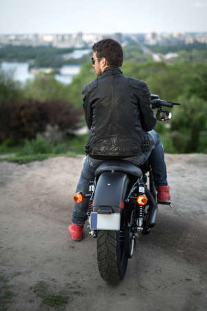 Rider sits on the black motorbike on the background of the river and the city. He looks to the left. He wears a blue ripped jeans, red sneakers, a black leather jacket and sunglasses. Photographed from the back. Outdoors. Vertical.