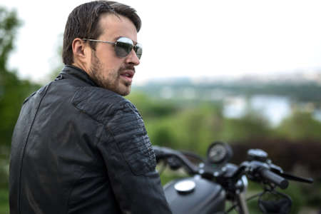 Trendy man sits on the black motorbike on the blurry nature background. He looks to the right with parted lips. He wears a black leather jacket and sunglasses. Photographed from the back. Outdoors. Horizontal.