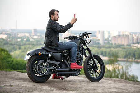 Stylish man with a beard sits on the black motorbike near the cliff on the background of the river and the city. He holds the red cellphone in his hands in front of himself. He wears a blue ripped jeans, red sneakers and a black leather jacket. There are