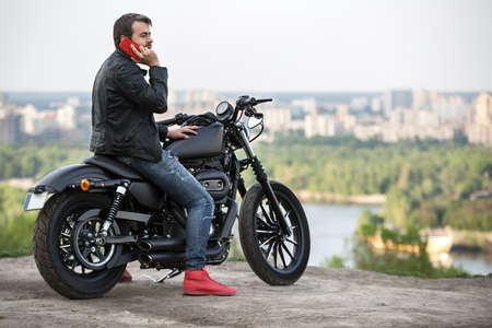 Cool man with a beard sits on the black motorbike near the cliff on the background of the river and the city. He talks on the red cellphone in his right hand. Left hand is on the motorbike. He wears a blue ripped jeans, red sneakers and a black leather ja Reklamní fotografie